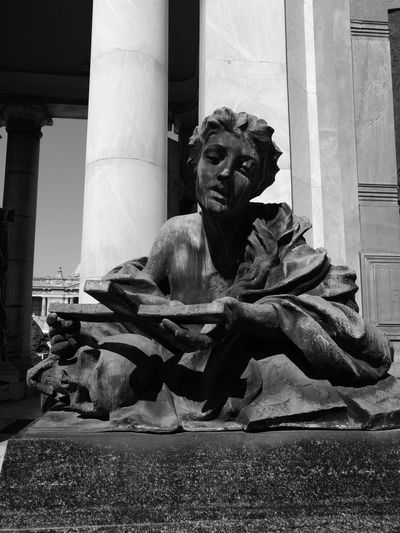 Statue of man sitting in front of building