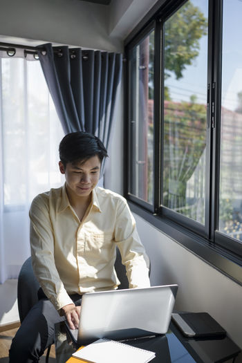 Mid adult man using mobile phone while sitting on window