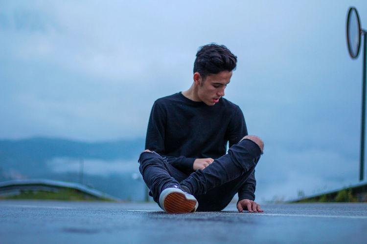 Boy Sitting Against Sky