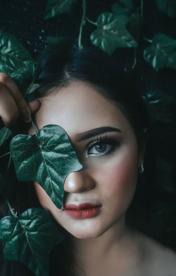 Portrait of young woman wearing make-up by plants
