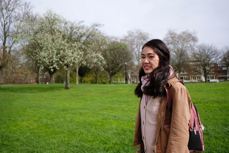 Happy young woman standing on grass against trees