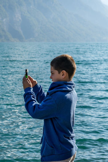 capturing boy Adults Only Blue Day Lake Lake View Mobile Conversations Mobile Phone Mountain Range Mountains One Person Outdoors People Sea Standing Switzerland Water מייעמית TCPM