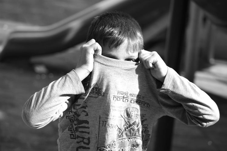 Boy Removing T-Shirt At Park