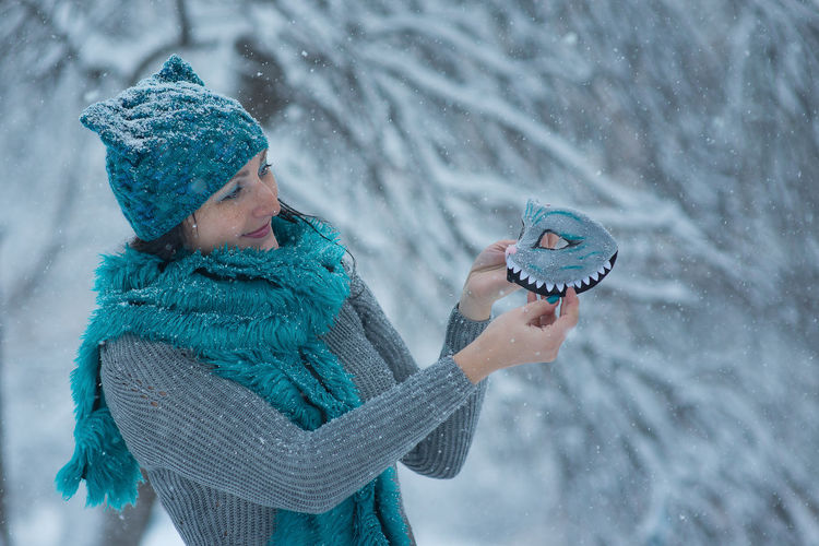 Woman holding eye mask during winter