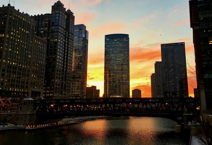 """Sunset reflects off of the Chicago River as an elevated """"el"""" train passes over the track in Chicago Loop during winter. Chicago Chicago River Chicago El Chicago Loop Downtown Chicago Elevated Track Architecture Bridge - Man Made Structure Building Exterior Built Structure City Cityscape Cloud - Sky Day Elevated Train Modern Outdoors River Sky Skyscraper Sunset Transportation Travel Destinations Urban Skyline Water"""