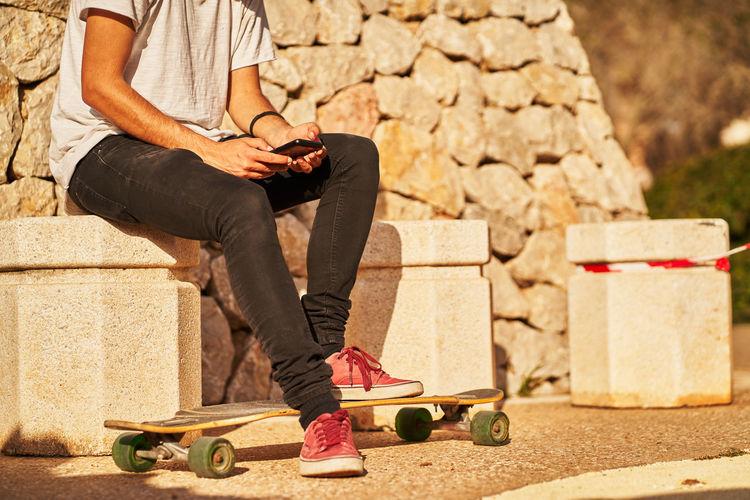 Man skateboarding on skateboard against wall