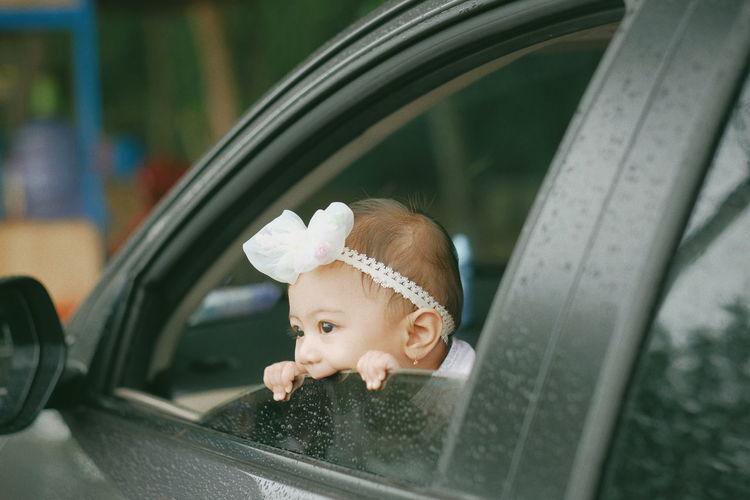 Little baby peeking outside car window