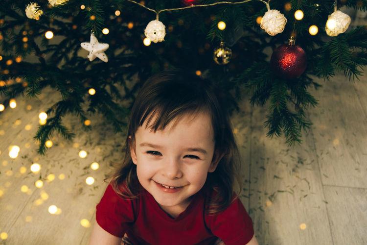 Portrait of happy girl in christmas tree