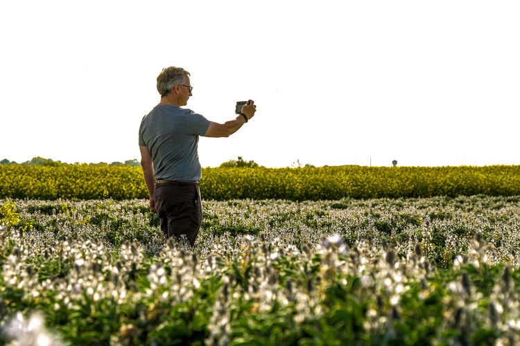 Man photographing on field against clear sky