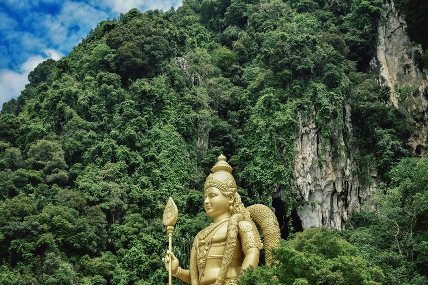 Batu Batu Caves Statue Human Representation Sculpture Male Likeness Tree Religion Idol Spirituality Growth Green Color No People Plant Nature Day Outdoors Beauty In Nature Sky Kuala Lumpur Kuala Lumpur Malaysia  Kualalumpur Malaysia The Week On EyeEm EyeEmNewHere Investing In Quality Of Life