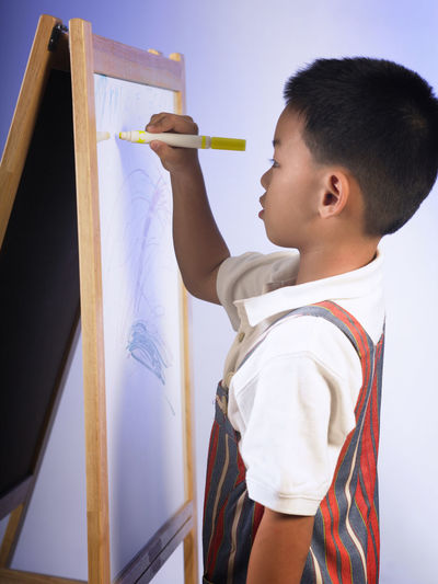 Boy drawing on canvas against wall