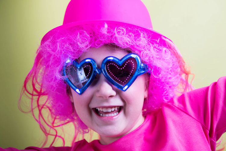 Portrait of happy girl with pink wig against yellow background