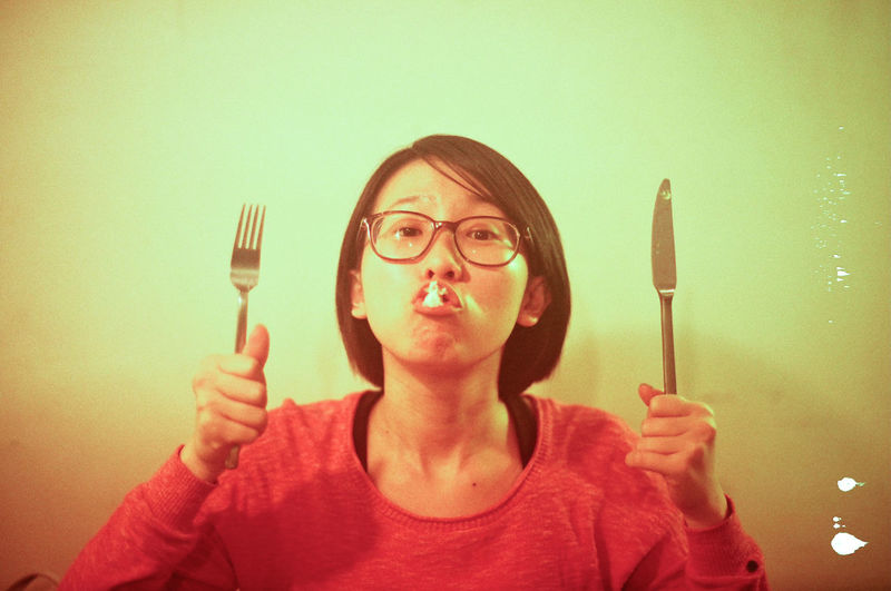 Portrait Of Young Woman Making Face While Holding Fork And Butter Knife At Home