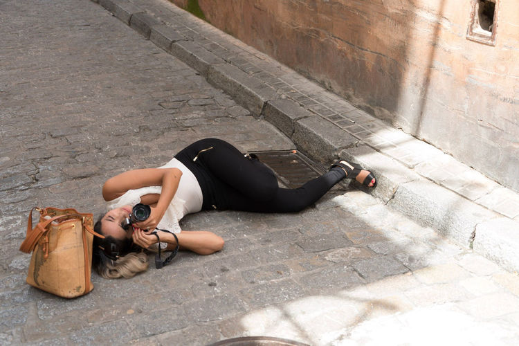 Woman photographing through camera while lying down on footpath