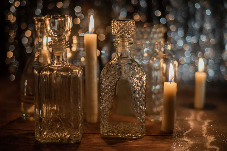 Close-up of candles burning by glass bottles on table