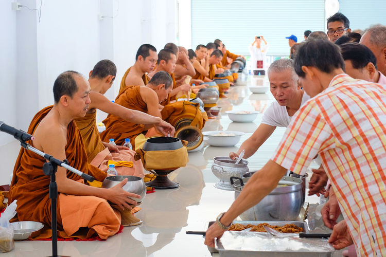 Buddhist Buddhist Monks Enjoyment Front View Holding Indoors  Large Group Of Objects Lifestyles Monks Occupation Perspective Portrait Real People Sitting Togetherness