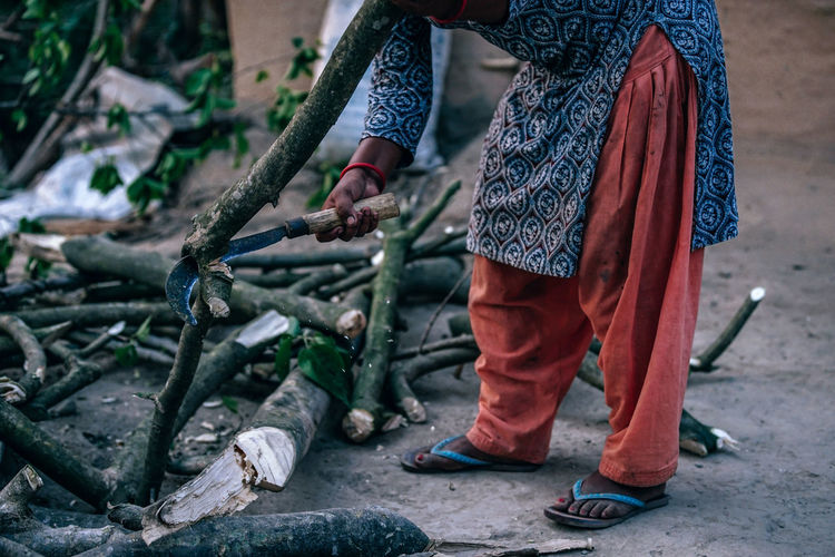 Village Woman Cutting Branch Cutting Tree Woman Adult Body Part Branch Casual Clothing Corncode Day Flora Holding Human Body Part Human Foot Human Leg Lifestyles Low Section Nature One Person Outdoors Real People Shoe Standing Village Women Working