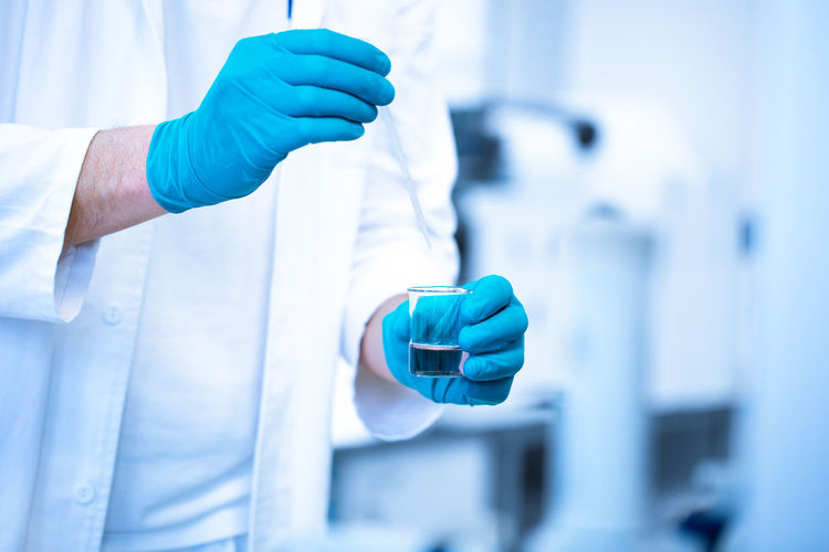 Midsection of scientist holding vial in laboratory