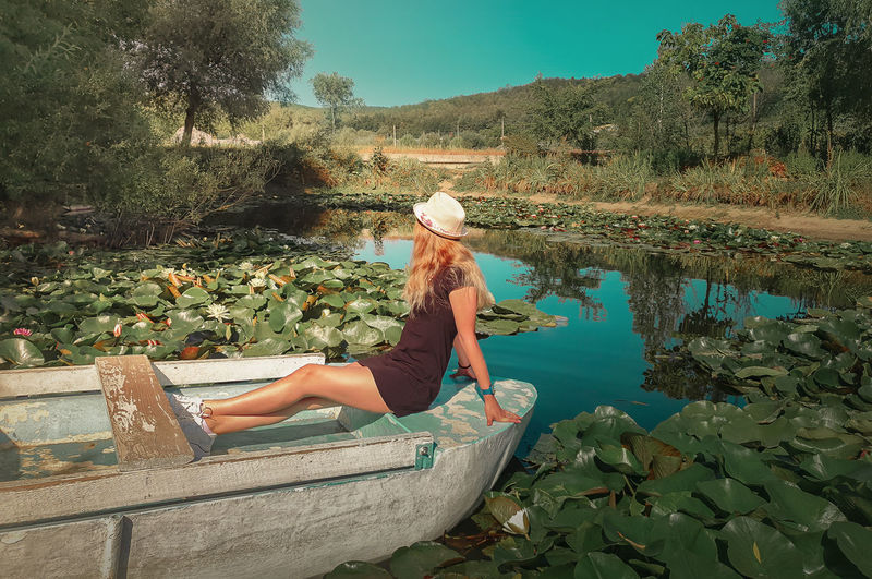 Carefree young woman floating relaxed on a boat at a pond with blooming waterlily, lotus flowers.