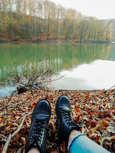Low section of man by autumn leaves in lake