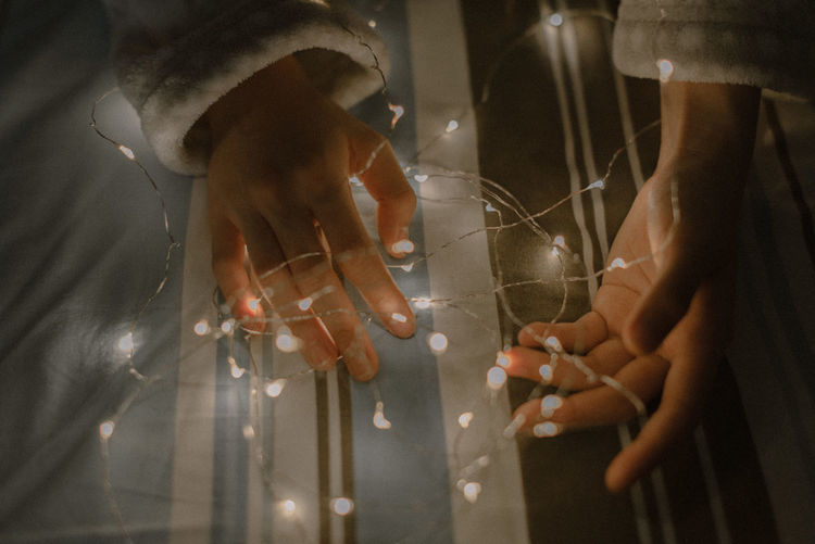 High angle view of hands with illuminated string lights on bed