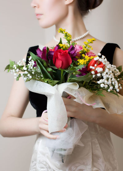 Midsection Of Woman Holding Colorful Bouquet Against White Background