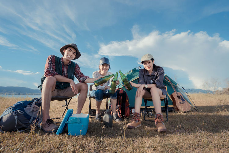 Portrait Of Friends Toasting Beer Bottles While Camping On Grassy Field Against Blue Sky