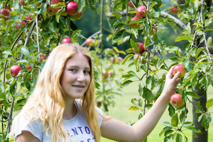 Appel Tree Apples Beutiful  Blond Casual Clothing Day Eating Girl Girls Growth Happiness Laugh Leisure Activity Lifestyles Long Hair Outdoors Person Plant Portrait Smiling Teenager Teenagers  Toothy Smile Tree Young Women