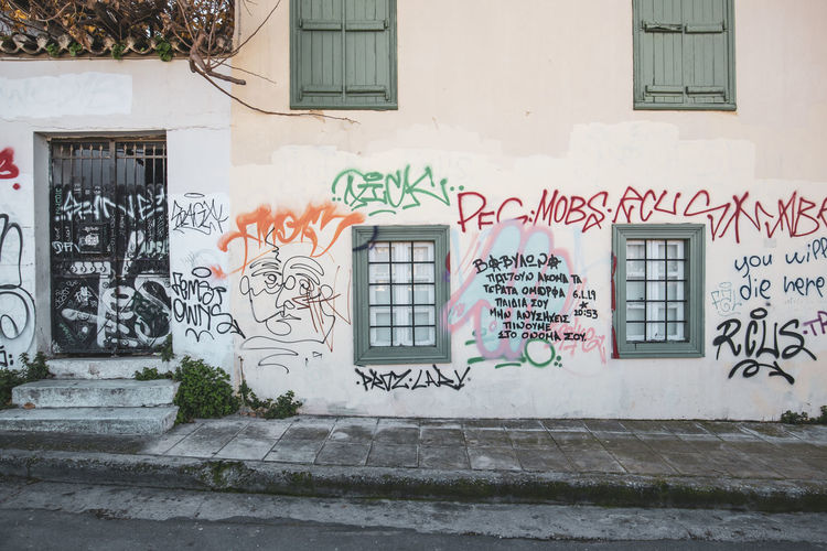 Athens Athens Greece Athens, Greece Acropolis Architecture Built Structure Building Exterior Graffiti Building Residential District City Creativity Day Window Text Art And Craft No People Outdoors Wall - Building Feature Communication Street Art Plant Multi Colored House