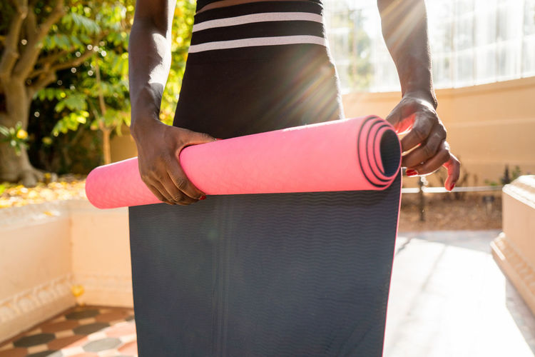 African woman holding yoga mat