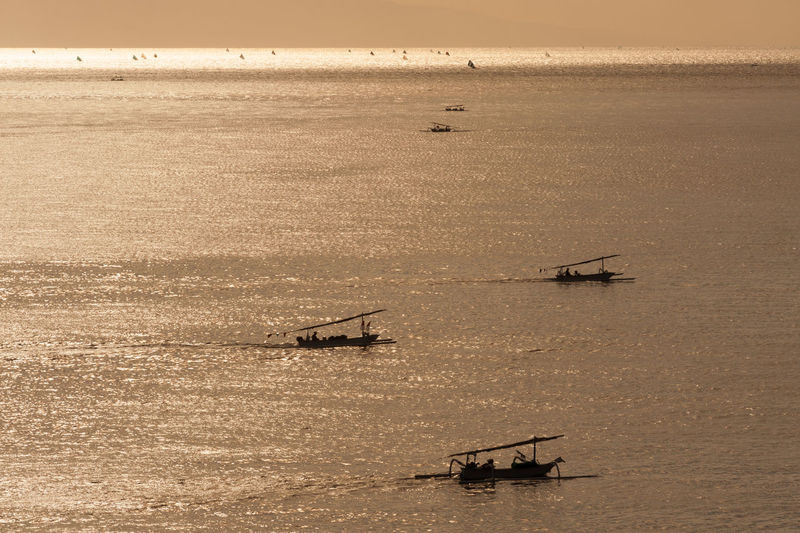 Bali Fishermen Returning Home. Fishermen return to shore after a night of fishing for mackerel and barracuda. Hundreds of these boats, called jukung, can be seen along the horizon with their sails up. Amed Asian Culture Bali Bali, Indonesia Balinese Beauty In Nature Fishermen Fishing Fishing Boat Fishing Village Jemeluk Jukung Lombok Strait Nature Ocean Outdoors Outrigger Scenics Sea Southeast Asia Sunrise Travel Destinations Tropical Tropical Paradise Water