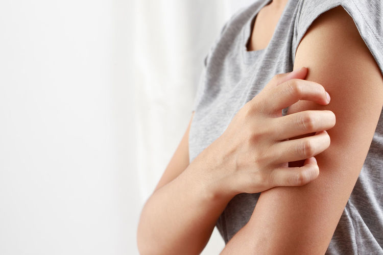 Midsection of woman touching finger