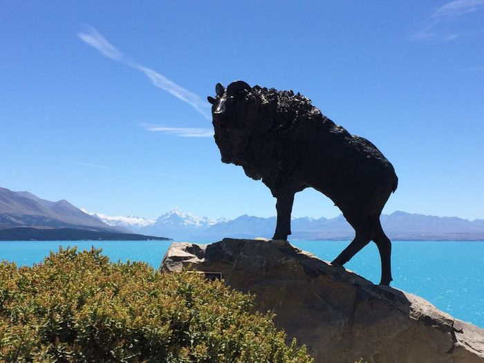 Low angle view of statue of rock against lake pukaki