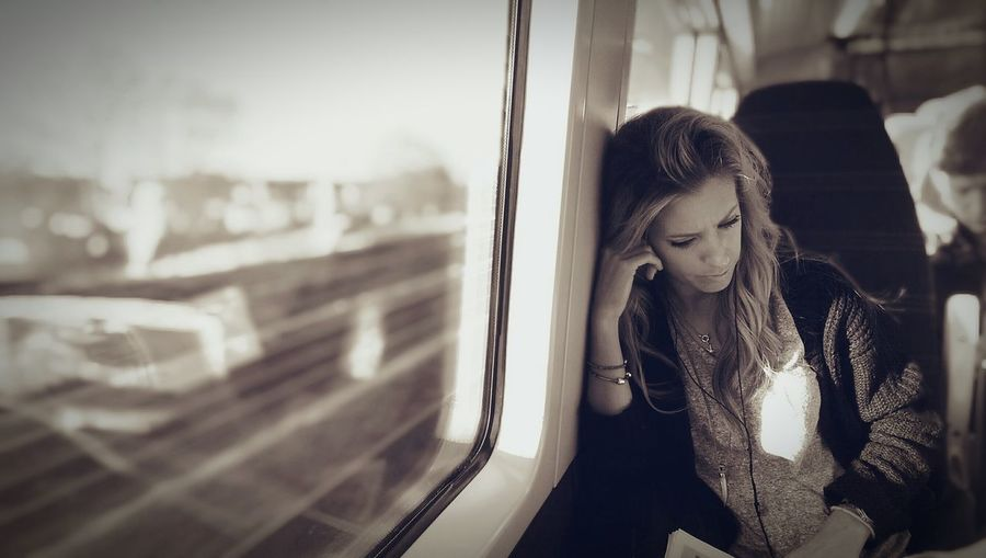 Woman looking down while sitting in train