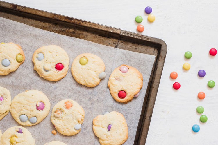 Homemade sugar cookies with colorful chocolate candies on white wooden background Chocolate Cookies Copy Space Homemade Sugar White Space Baking Chocolate Candies Chocolate Candy Close-up Smarties Sugar Cookies White White Background Wooden Background