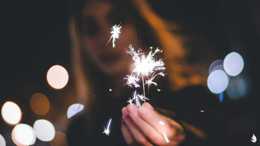 Low angle view of woman burning sparkler while standing on street at night