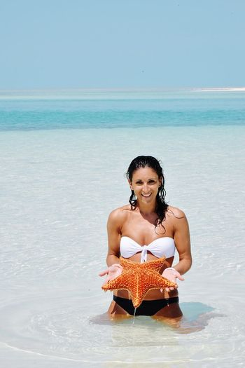 Portrait of smiling young woman holding starfish at beach