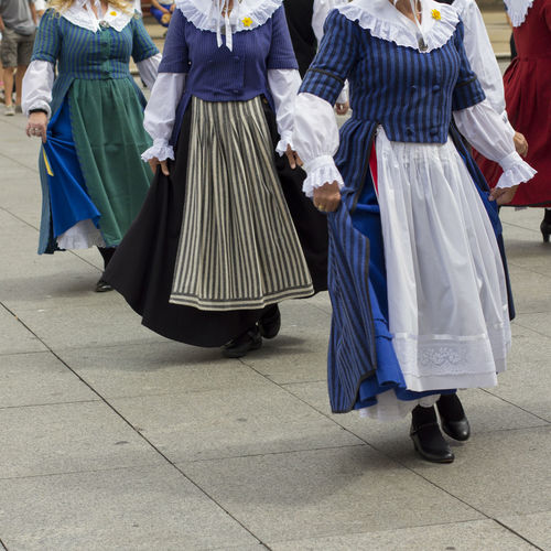 Midsection of women walking on street during festival