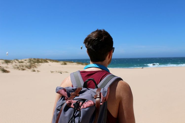 Rear View Of Young Man With Backpack Standing At Beach Against Blue Sky During Sunny Day
