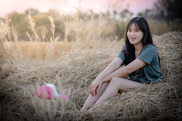 Portrait of a smiling young woman sitting on field
