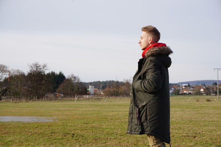 Side view of man looking away while standing on grass against sky