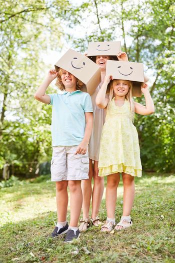 Happy Woman With Children Holding Cardboard Boxes While Standing In Park