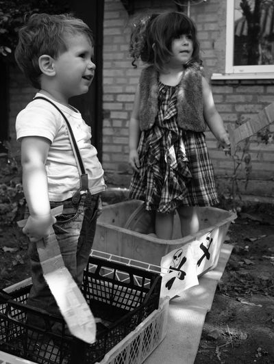 Cute Siblings Holding Swards While Standing In Baskets