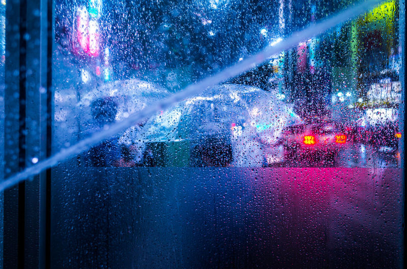 Close-up of wet window in illuminated city at night during rain