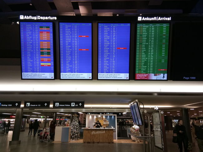 Airport Indoors  Arrival Departure Board Travel Real People Architecture Illuminated Group Of People Text Communication People Incidental People Transportation Built Structure Western Script Technology Sign Public Transportation Transportation Building - Type Of Building Men Airport Terminal Waiting