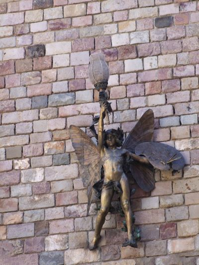 Unusual Outdoor Light Fitting Architectural Feature Barcelona City Composition Fairy Feature Full Frame Fun Human Representation Light Light Fitting No People Ornate Design Outdoor Photography Spaın Stone Wall Tourism Tourist Attraction  Tourist Destination Unsual Wall - Building Feature Wall Decoration Weathered Wings