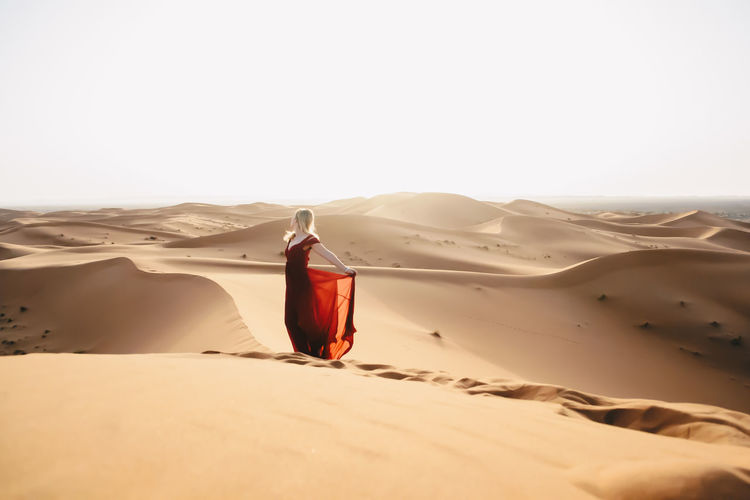 Alone in the desert Alone Blonde Desert Dress Dunes Feminine  Hot Morocco Red Travel Woman Arid Climate Day Desert Landscape Nature Outdoors Sahara Sand Sand Dune Sandy Sky Solo Solo Travel Travel Destinations