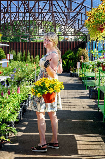 Full length of a woman standing by flower