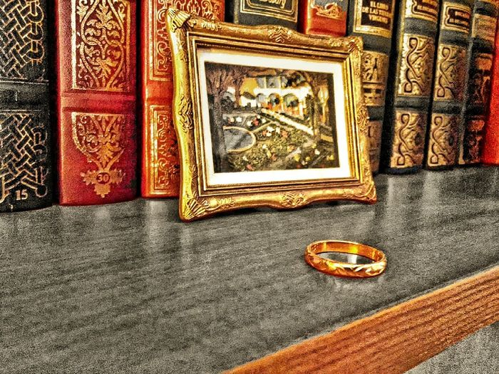 In the foreground, gold ring on book shelf highlighted in gray, behind post-impressionist reproduction. Background old books with deluxe binding. Bookshelves Classical Literature Close-up Colorful Divorce Divorced Gold GOLD RING Gold Wedding Ring Horizontal Indoor Loneliness Loneliness And Sadness Marriage  Old Books Picture Frame Post-Impressionism Single Single Life  Vintage Wedding Widower Widowhood Without Obligation