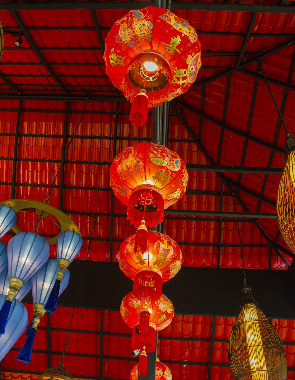 LOW ANGLE VIEW OF ILLUMINATED LANTERNS HANGING ON CEILING IN ROW